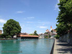 Da vorne ist die Stadt schon gut sichtbar. In der Bildmitte eine gedeckte Holzbrücke, über der Stadt das Schloss, darüber Blauhimmel