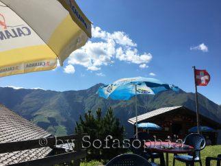 Alp Bischola-Bergrestaurant: Sonnenschirme unter Blauhimmel in Bergumgebung